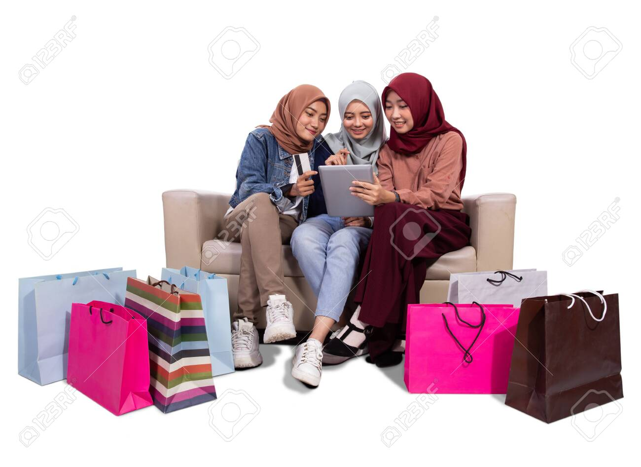 Three veiled women while sitting near paper bags and holding credit card to buying at an online shop - 128977751