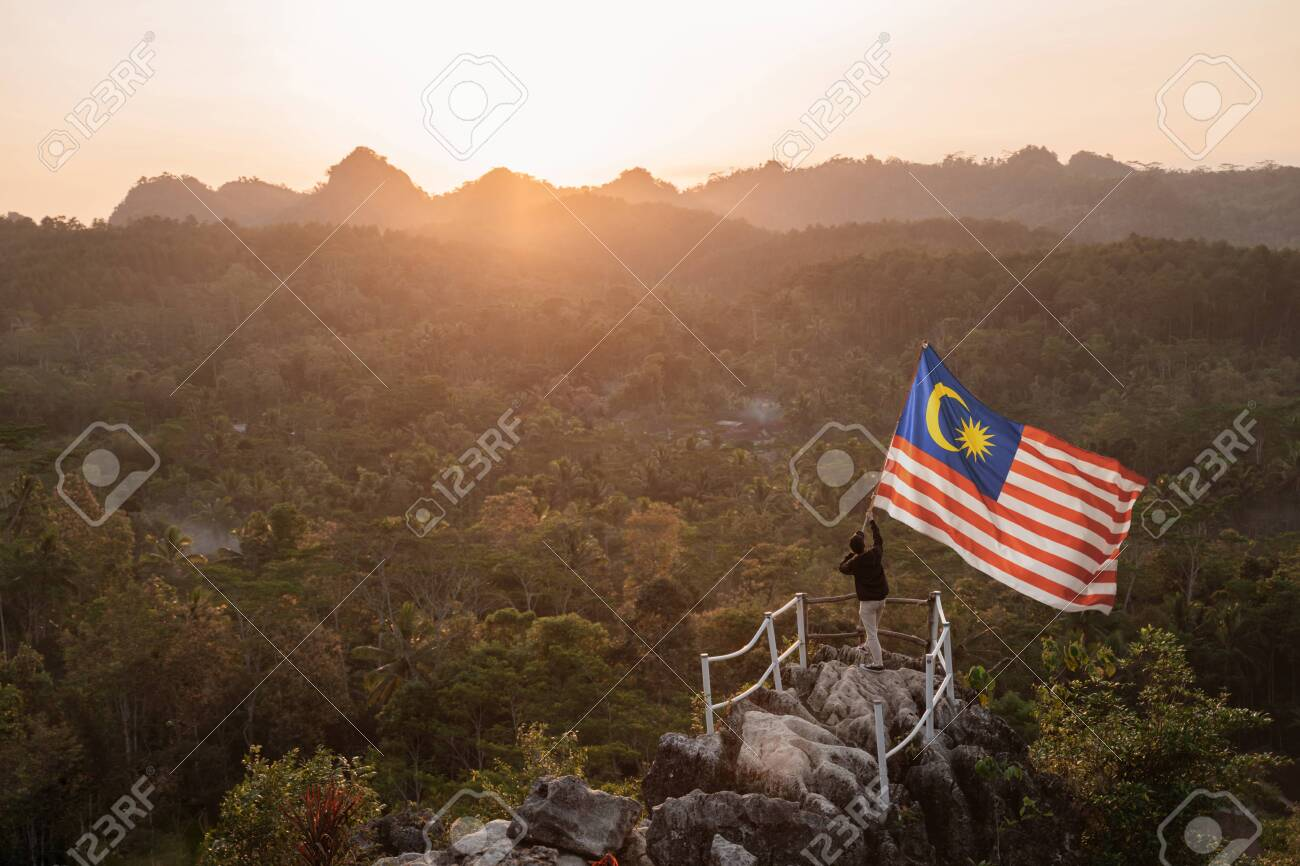 man with malaysian flag of malaysia on top of the mountain - 128978885