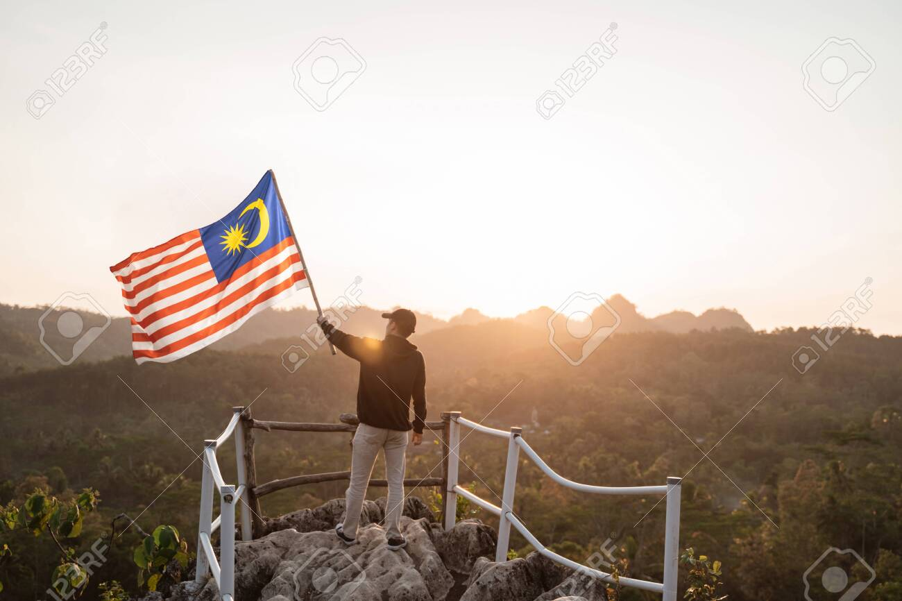 man with malaysian flag of malaysia on top of the mountain - 128584203