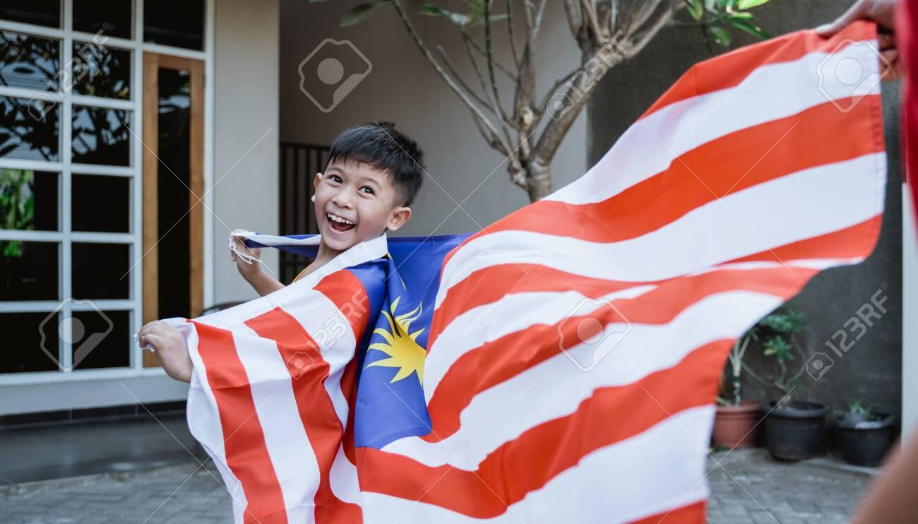 Malaysian kid with flag running - 128600747