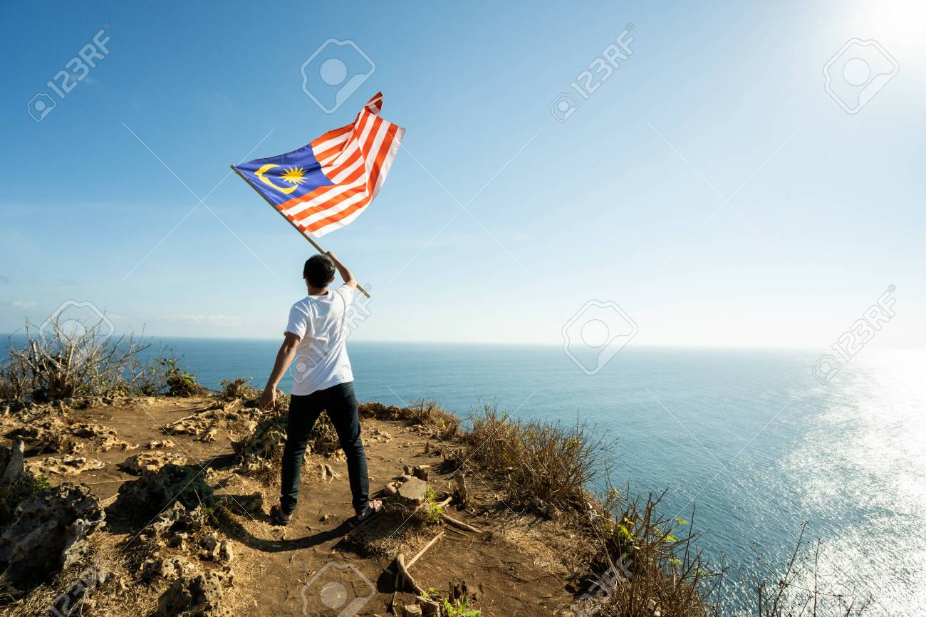 man with Malaysia flag of on top of the mountain - 128961194