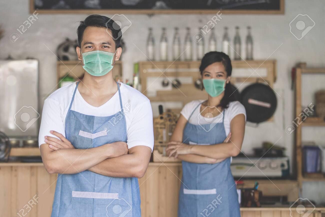 waitress at the shop wear face masks - 145163401