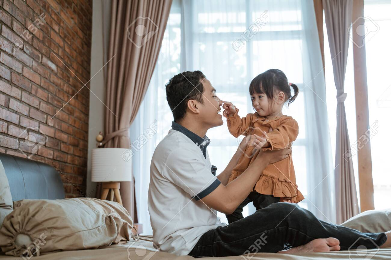 father laughed happily when his nose was touched by the little girl - 150552645