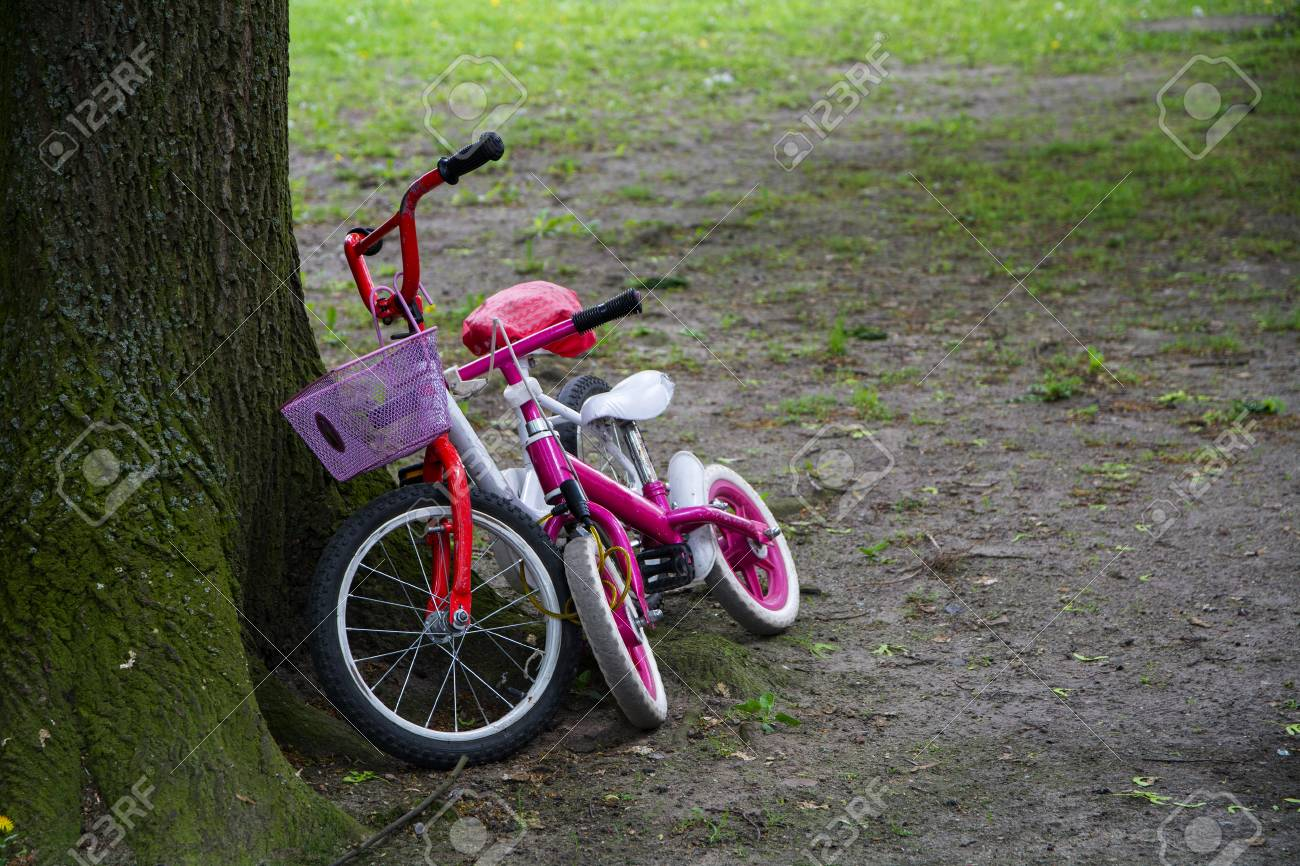 two children's bikes in red and pink leaning side by side at