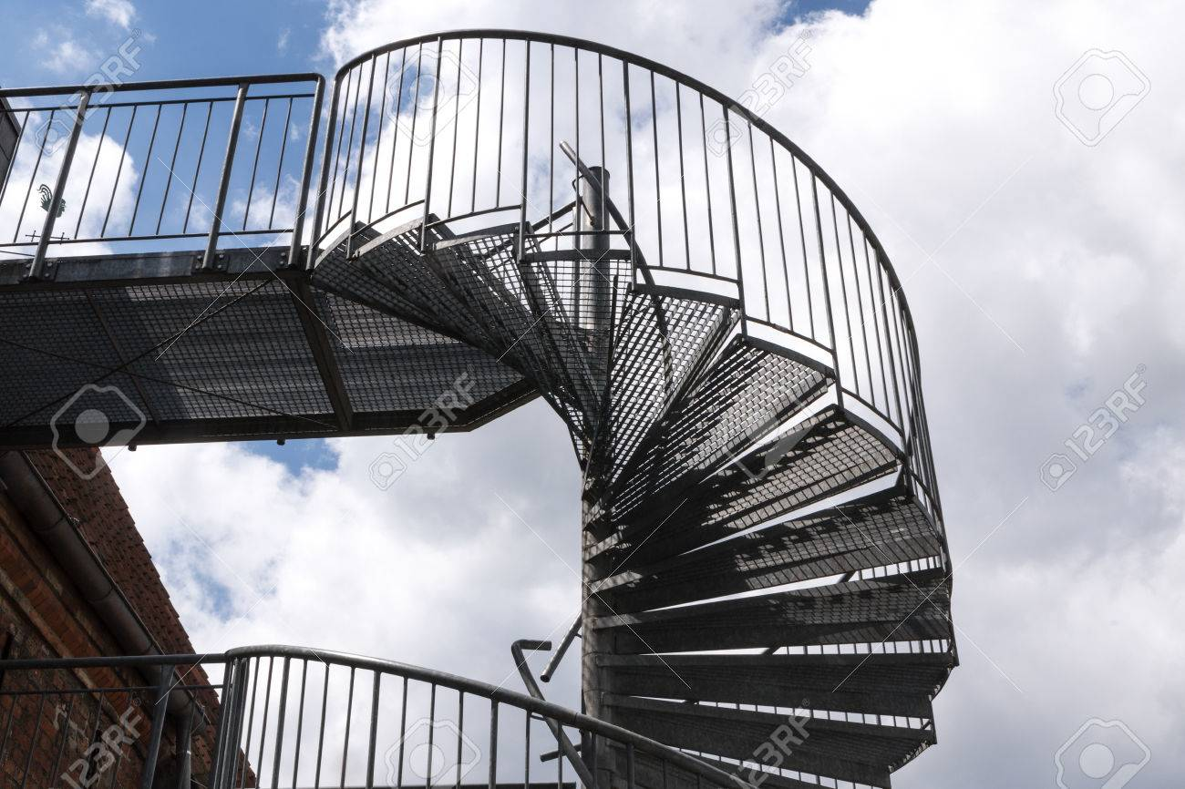 Modern Exterior Spiral Staircase From Metal At An Old Building Against A  Cloudy Sky Stock Photo