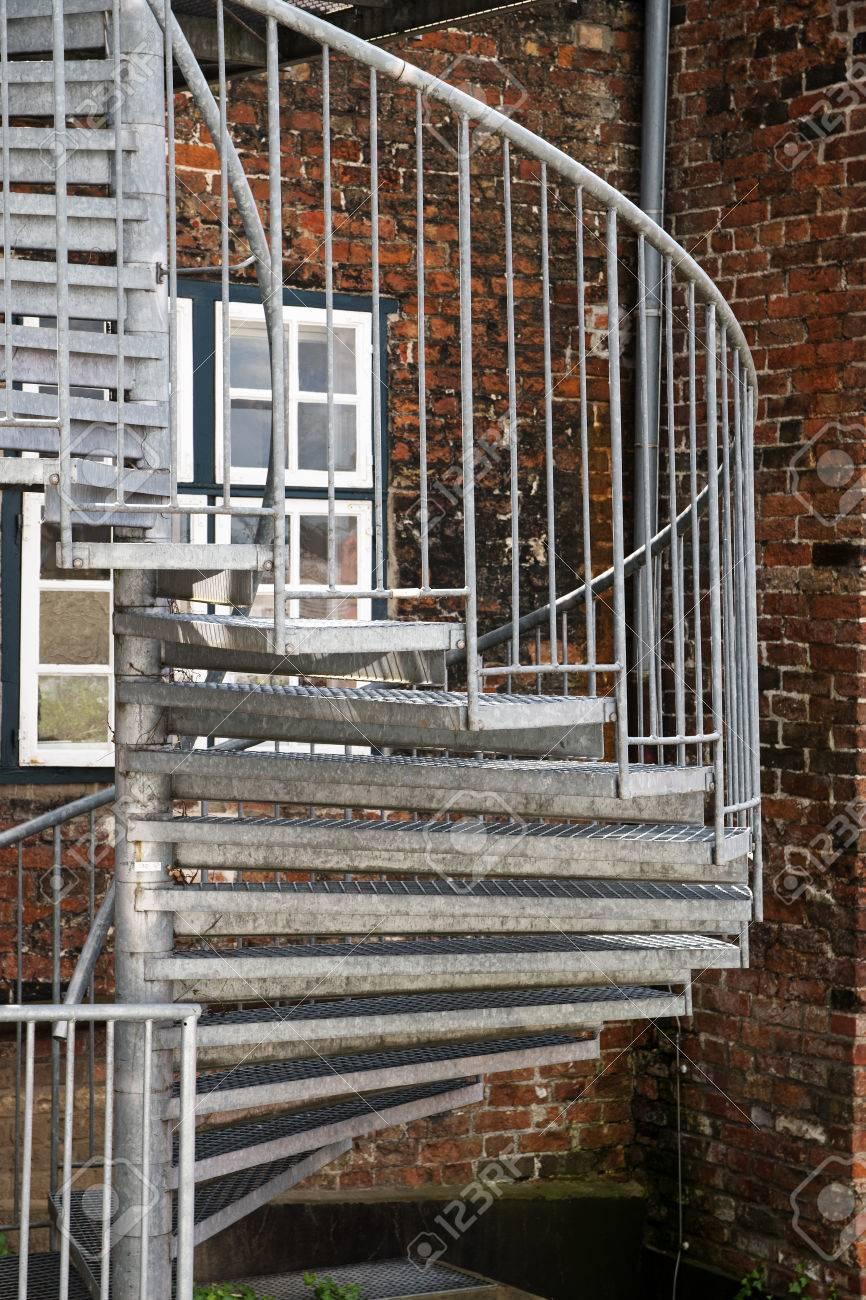 Escalier en colimaçon extérieur moderne en métal dans l\'arrière-cour sur un  vieux bâtiment en briques, escalier de secours dans la vieille ville