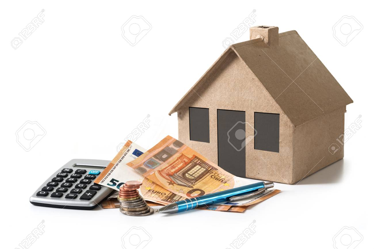 Money And Calculator In Front Of A House Model From Cardboard