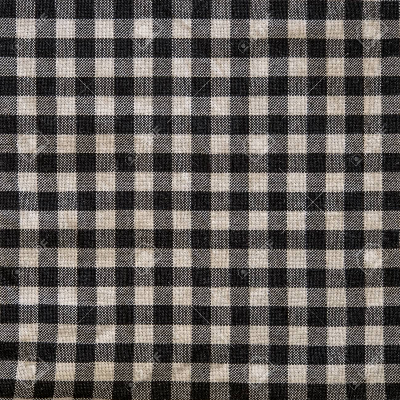 Gentil Close Up On Checkered Tablecloth Fabric. Black With White Tartan Square  Pattern As Background.