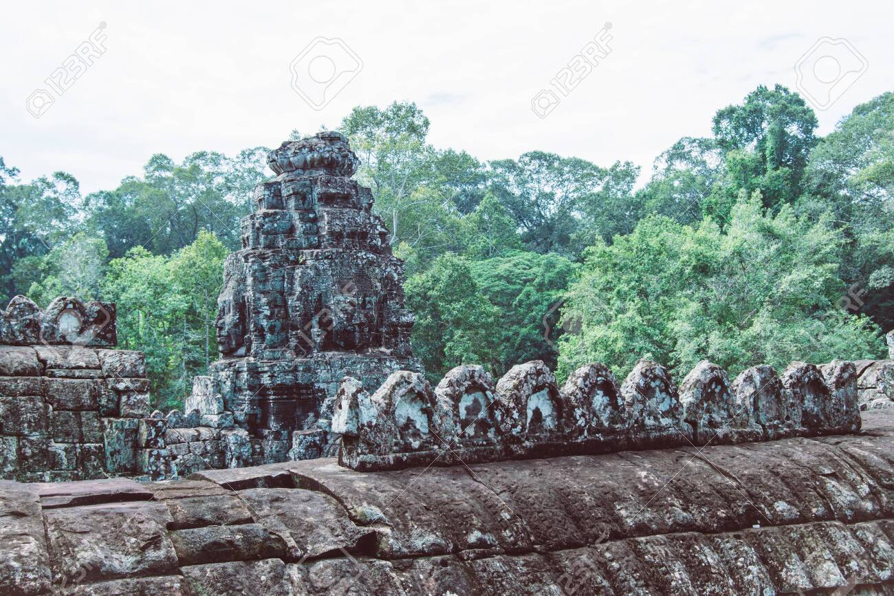 Sculptures made in rustic rocks on the roofs of the ruins of the Bayon temple in Ankgor Thom, Cambodia - World Heritage by UNESCO in 1992 - Colorful Photo - 128724072