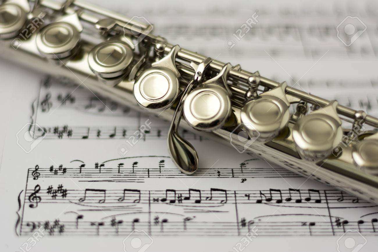 Close up flute on flute sheet music background