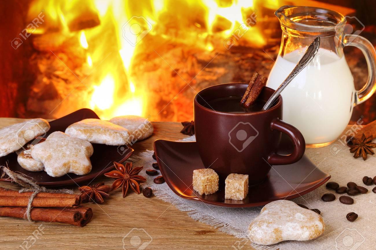 Foto Di Un Camino Acceso caffè con spezie, latte e torte sullo sfondo di un caminetto acceso