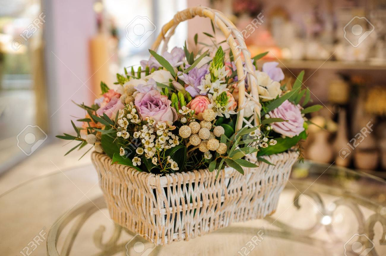 Beautiful bouquet of mixed flowers in basket on glass table royalty beautiful bouquet of mixed flowers in basket on glass table stok fotoraf 55076680 izmirmasajfo