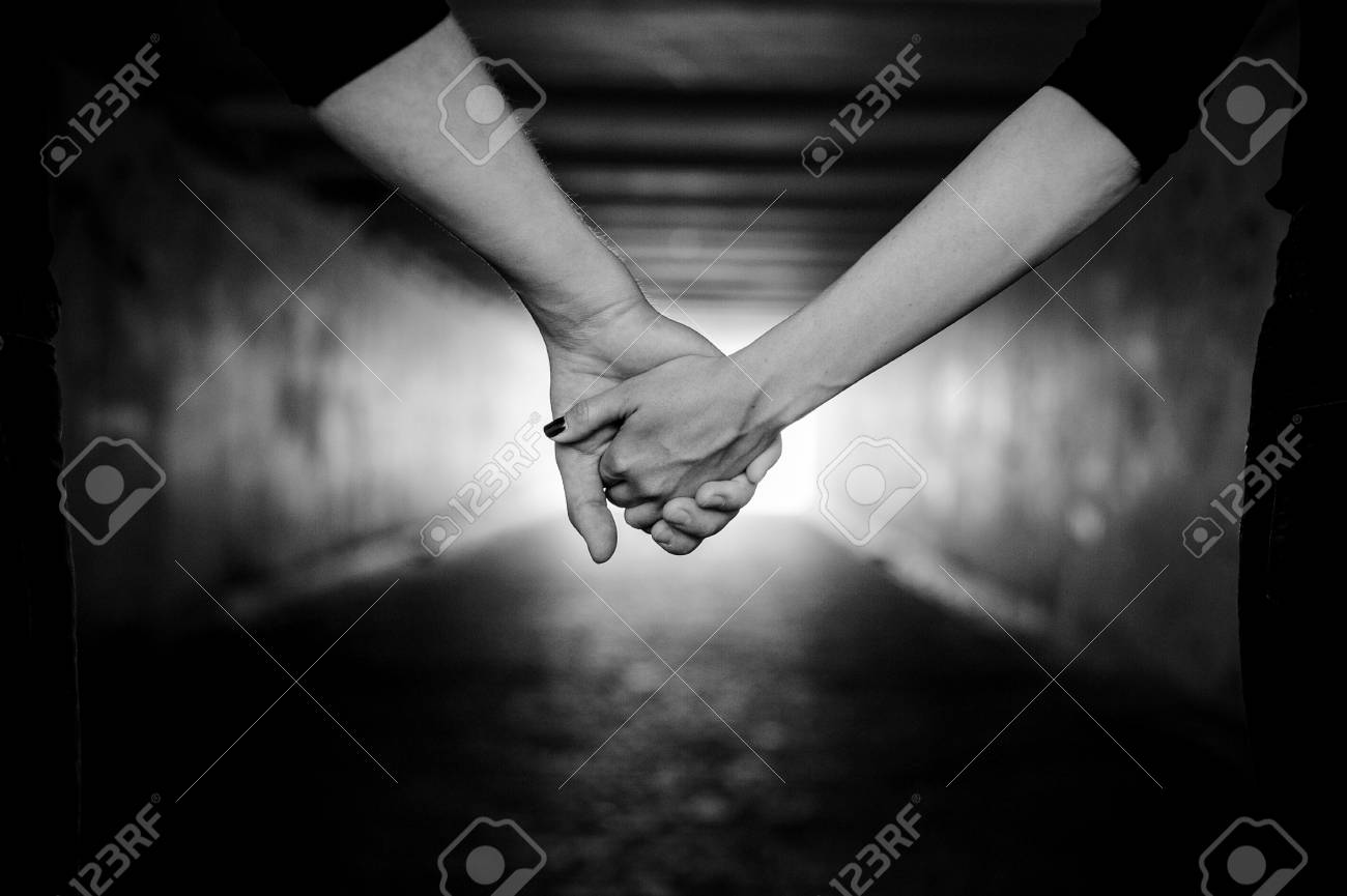 Happy couple holding hands black and white stock photo 64370421