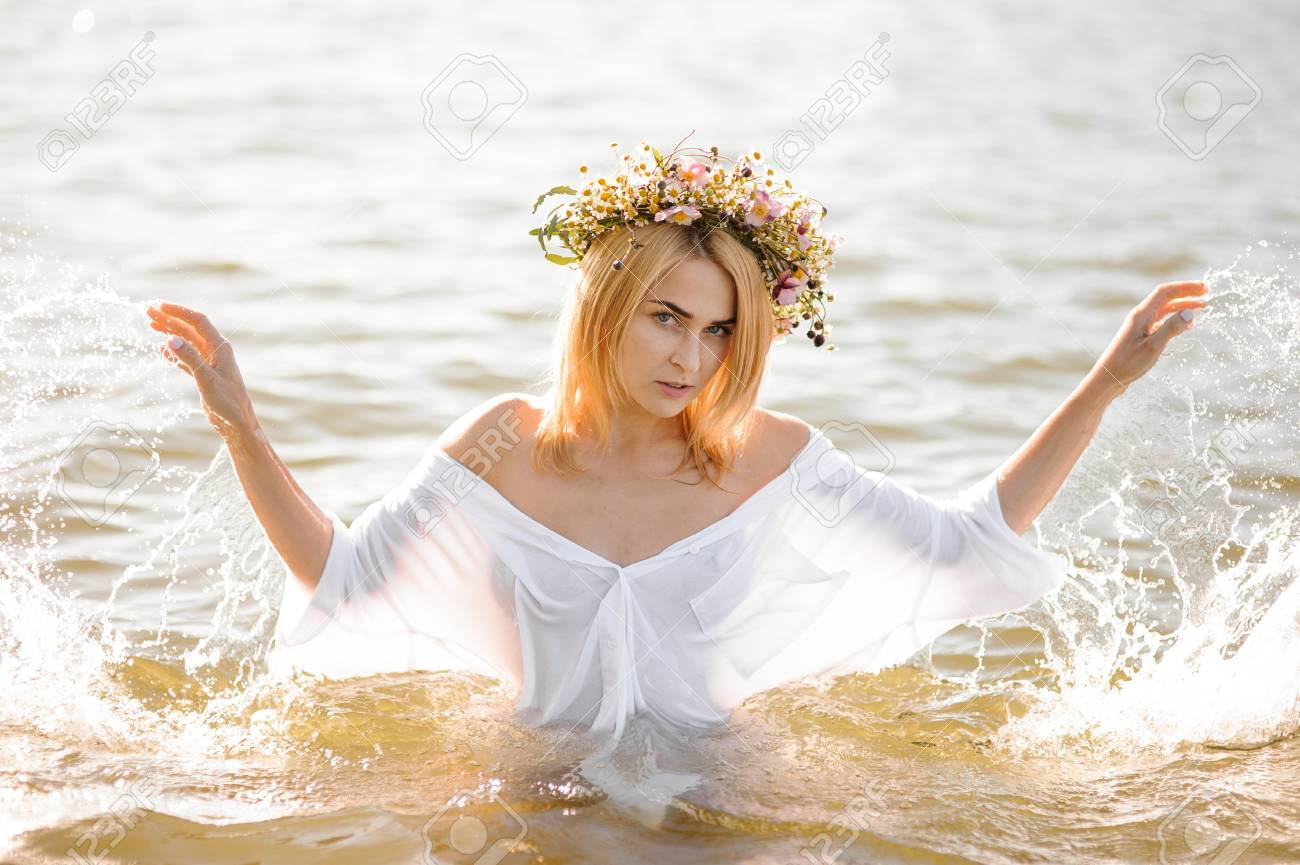 42fefd73 Portrait of a beautiful girl in a white wet shirt and floral wreath  standing in water