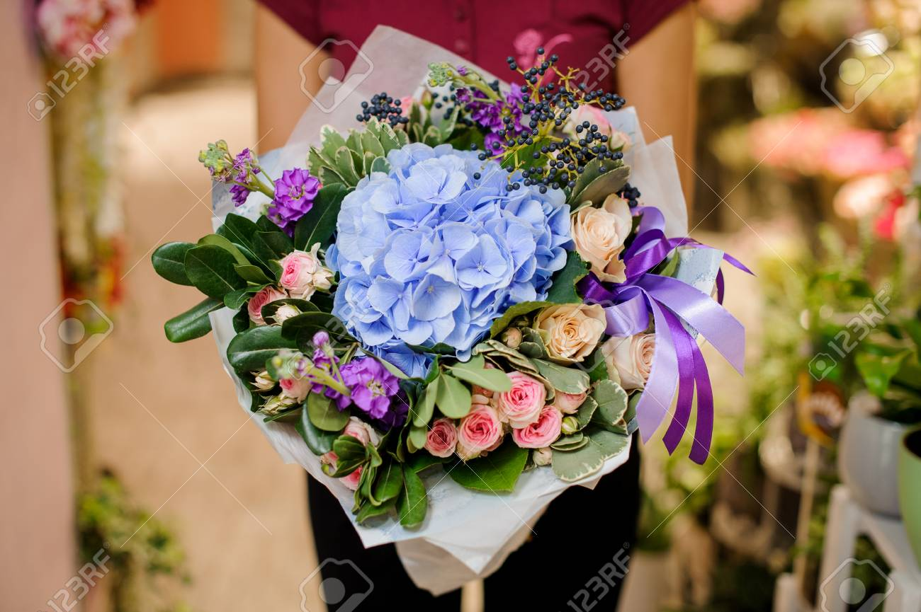 Refined and elegant bouquet of beautiful flowers in woman hands on the  light indoors background Stock 6c7e8c8c7f