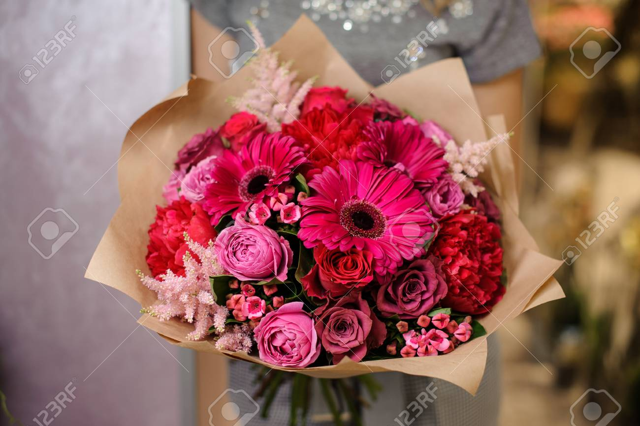 Woman Holding A Bright Pink Flower Bouquet Wrapped In Paper For