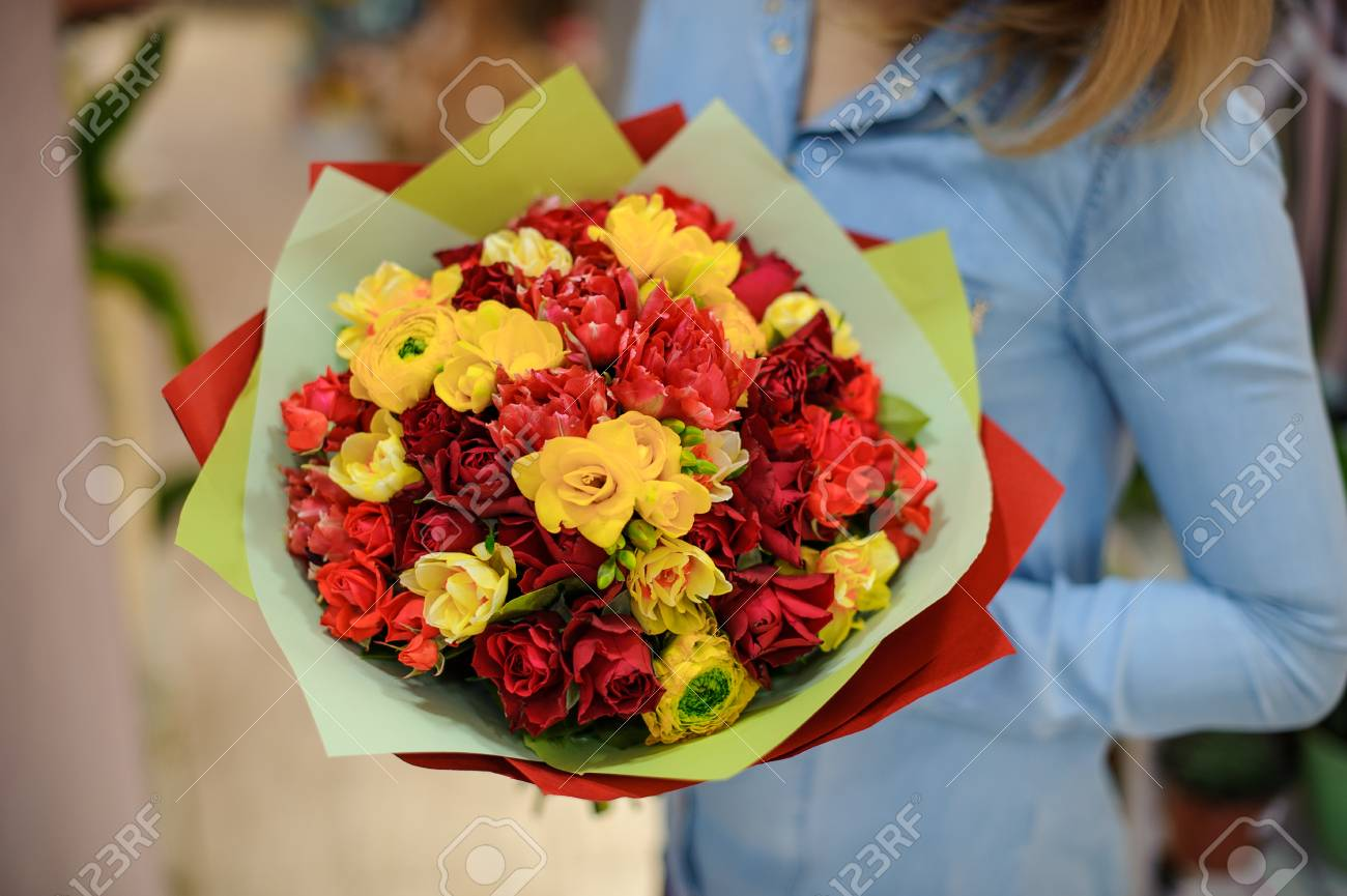Woman in a blue shirt holding a bright yellow and red flower stock stock photo woman in a blue shirt holding a bright yellow and red flower bouquet for valentines day izmirmasajfo