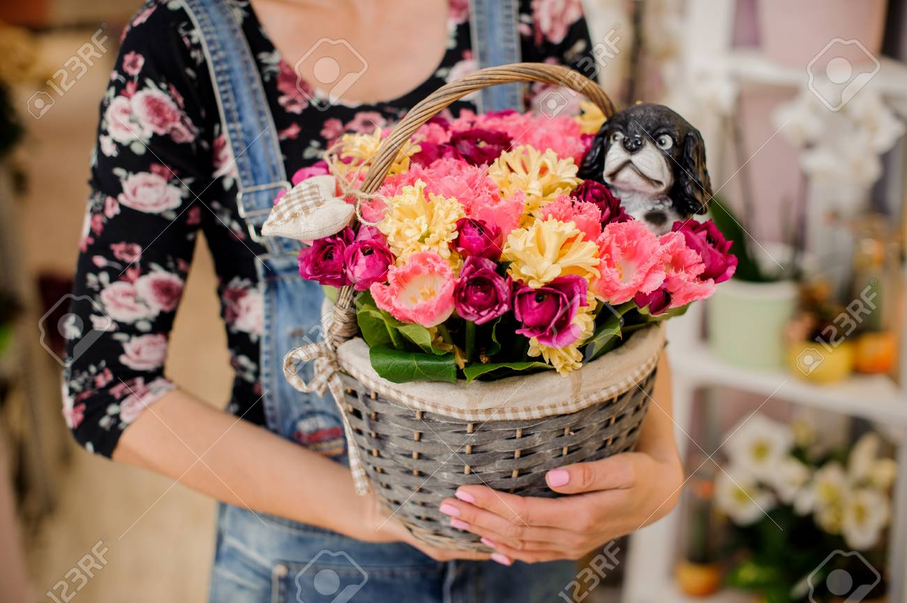 Girl holding a beautiful wicker basket with colorful flowers stock girl holding a beautiful wicker basket with colorful flowers and toy dog for valentines day stock izmirmasajfo