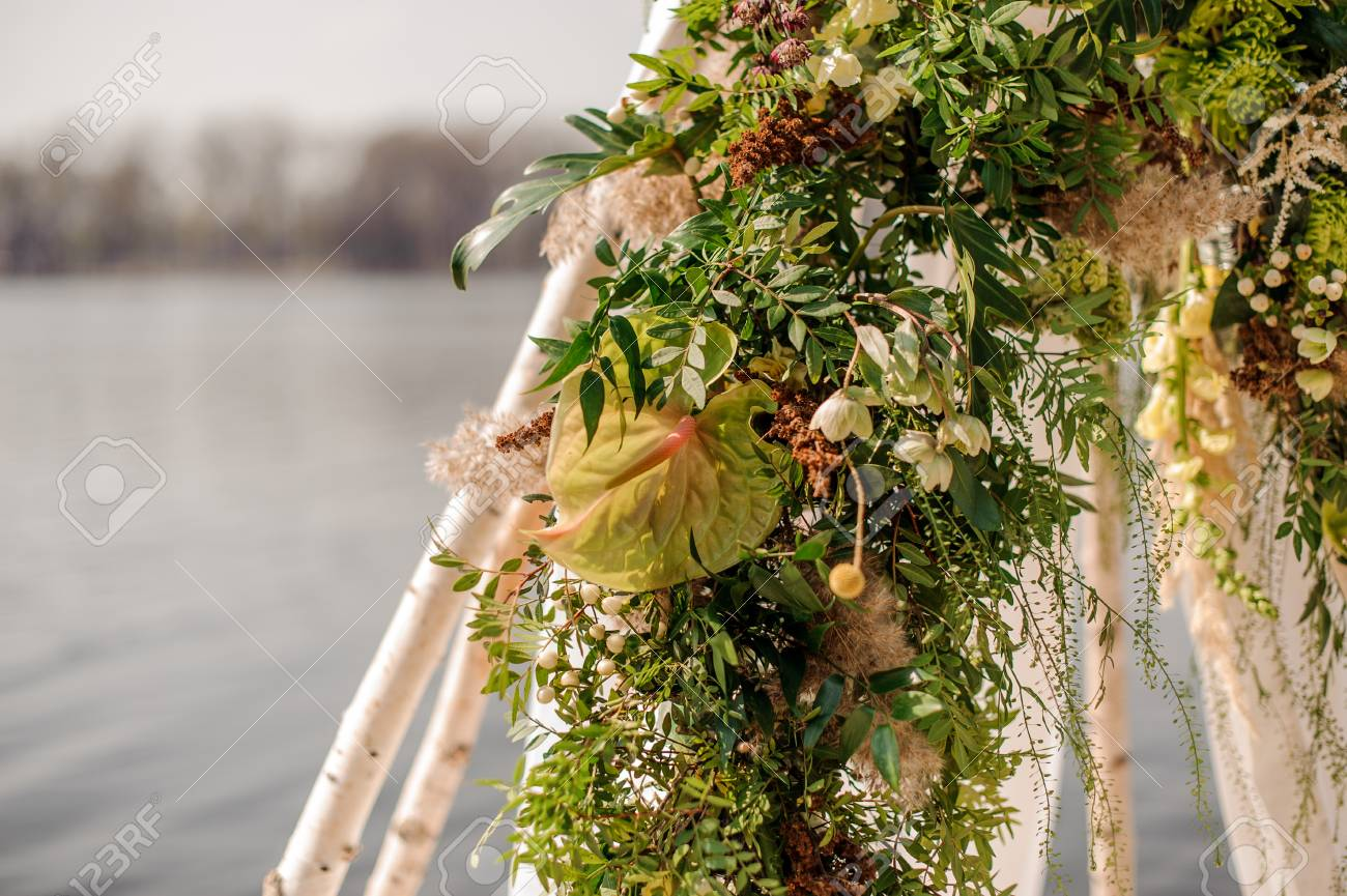 Tender wedding arch decorated with fresh tropical flowers and stock photo tender wedding arch decorated with fresh tropical flowers and white fabric on the river bank junglespirit Image collections