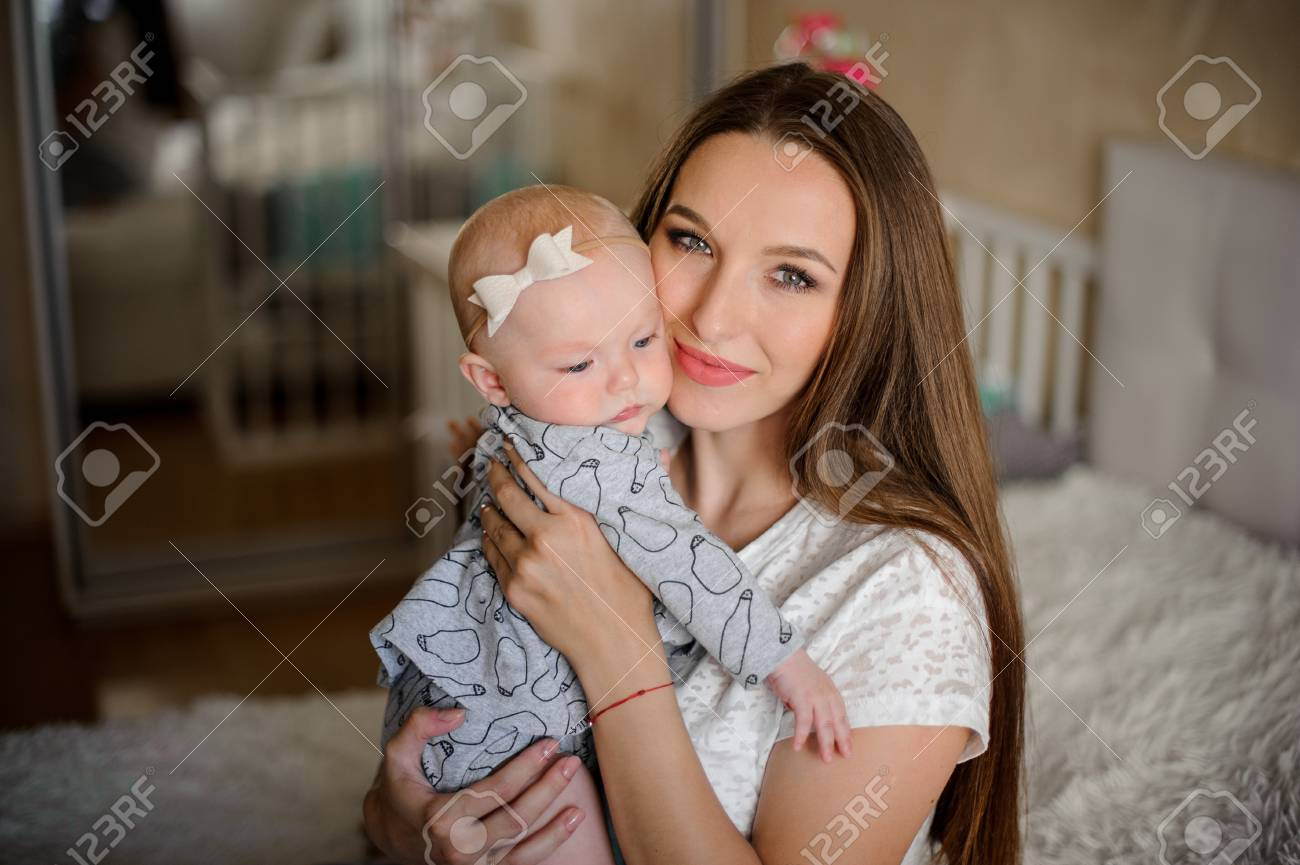 Stock Photo Young Brunette Mom Holding Her Little Blondie Daughter On Hands In Their Sweet Room On The Blurred Background