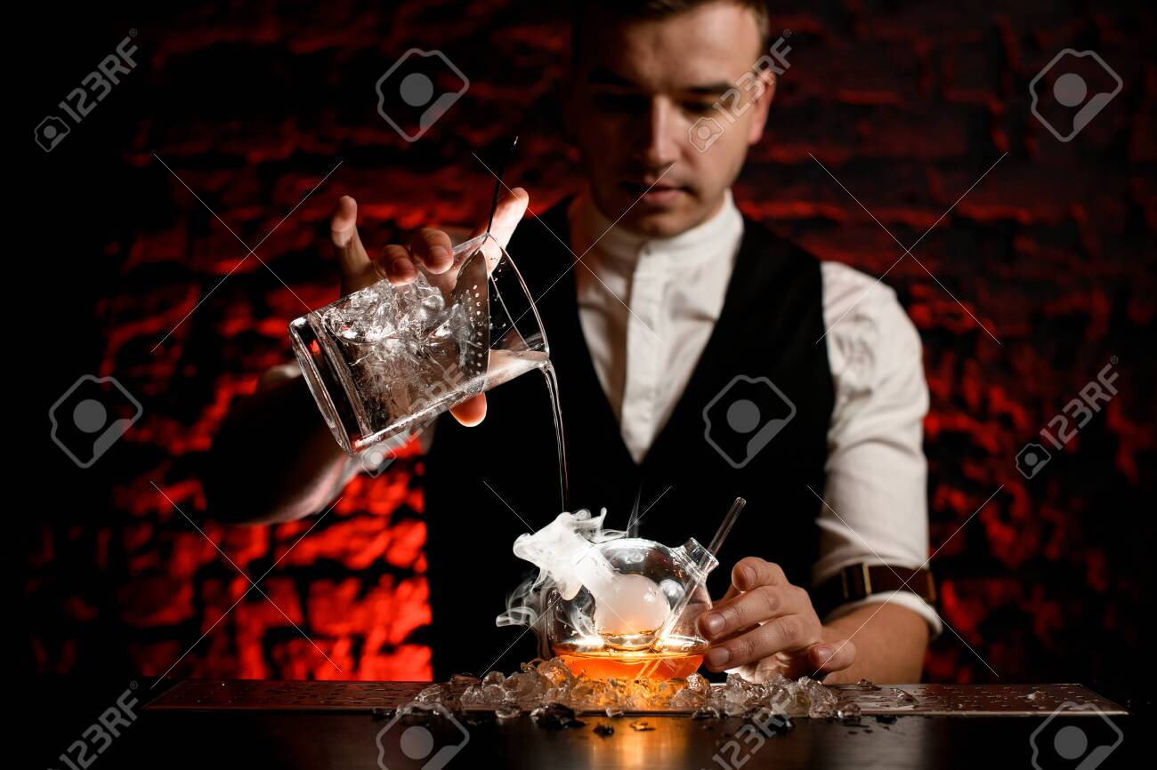 Man barman professionally pours cold drink into smoky designer flask - 145022579