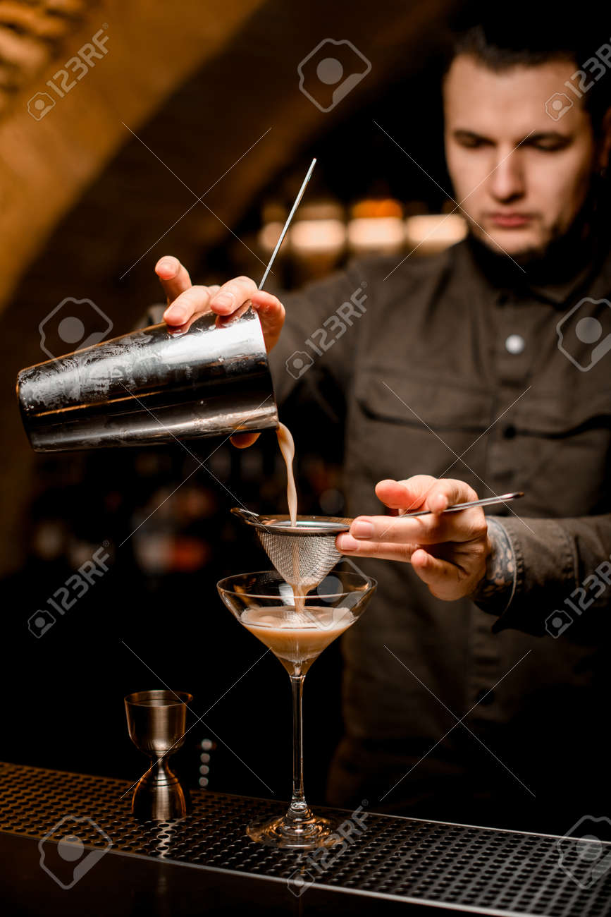 man bartender holds sieve and pours cocktail through it from shaker into glass - 168069117