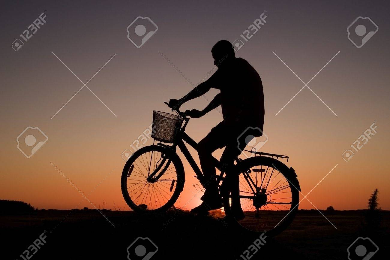 Man and  bike  silhouette in orange sunrise Stock Photo - 1261367