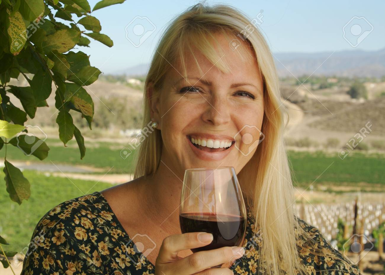 Beautiful smiling woman at a country winery tasting wine on a summer day. Stock Photo - 1311475