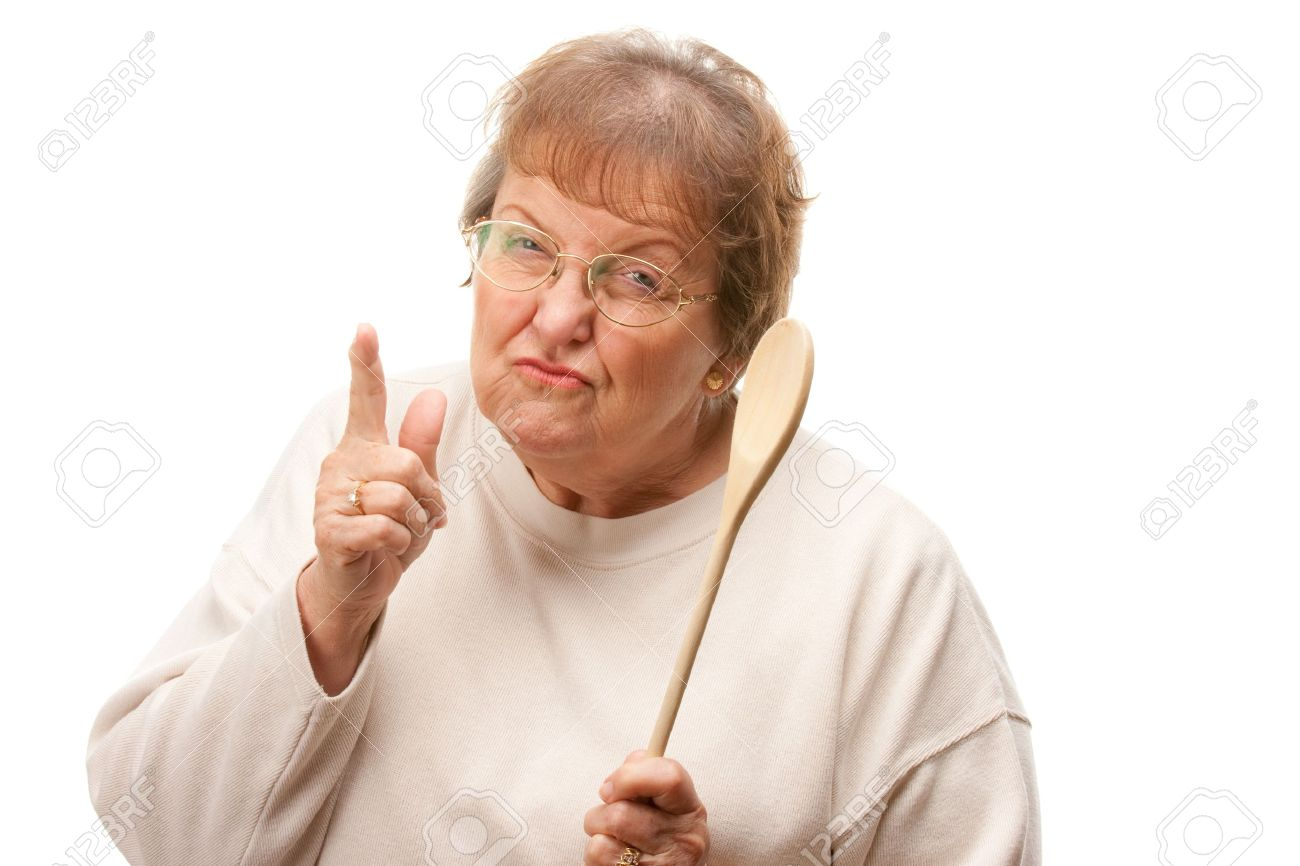 Upset Senior Woman with The Wooden Spoon Isolated on a White Background. Stock Photo - 4176199