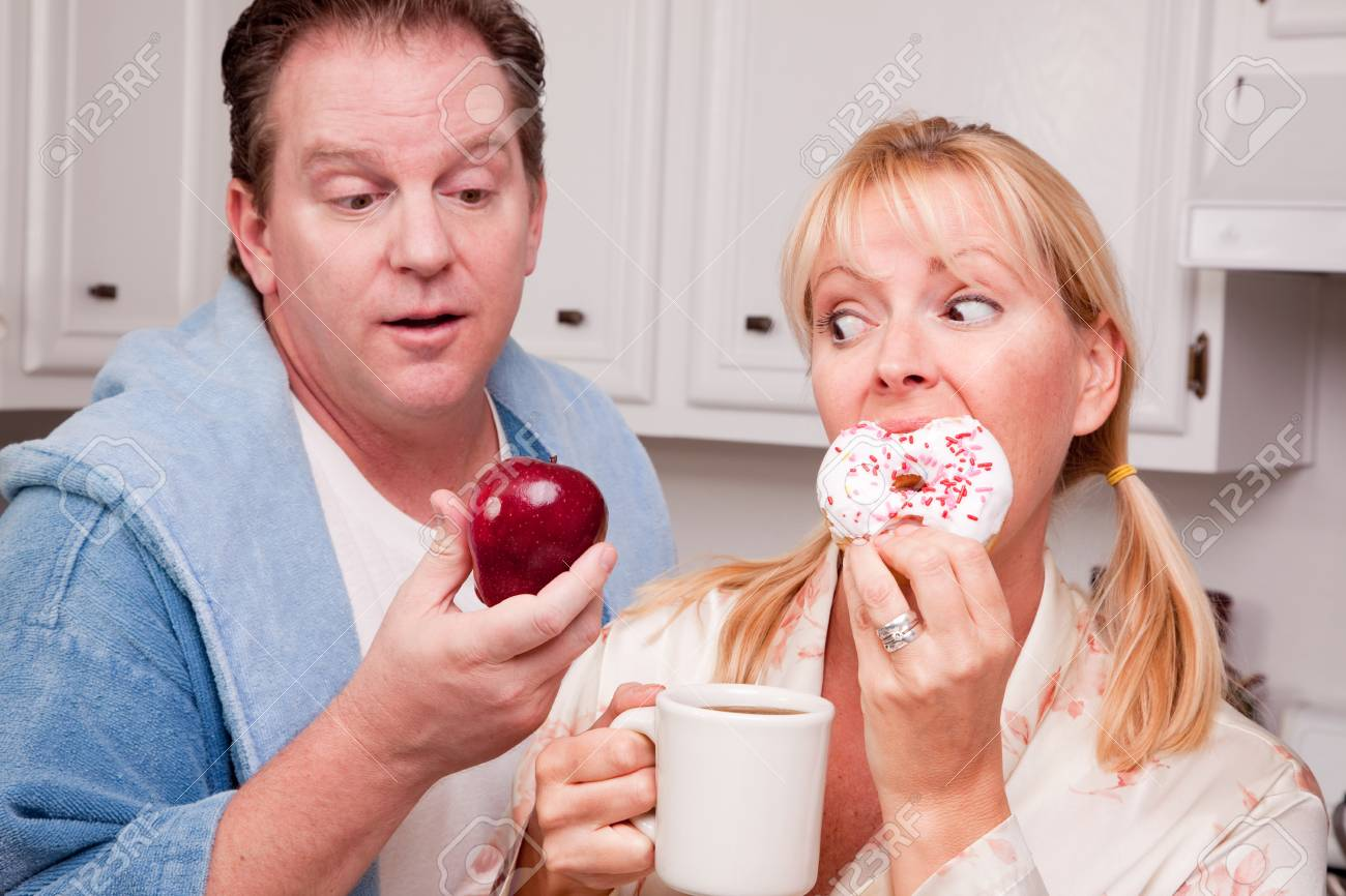 Couple in Kitchen Eating Donut and Coffee or Healthy Fruit. Stock Photo - 4391925