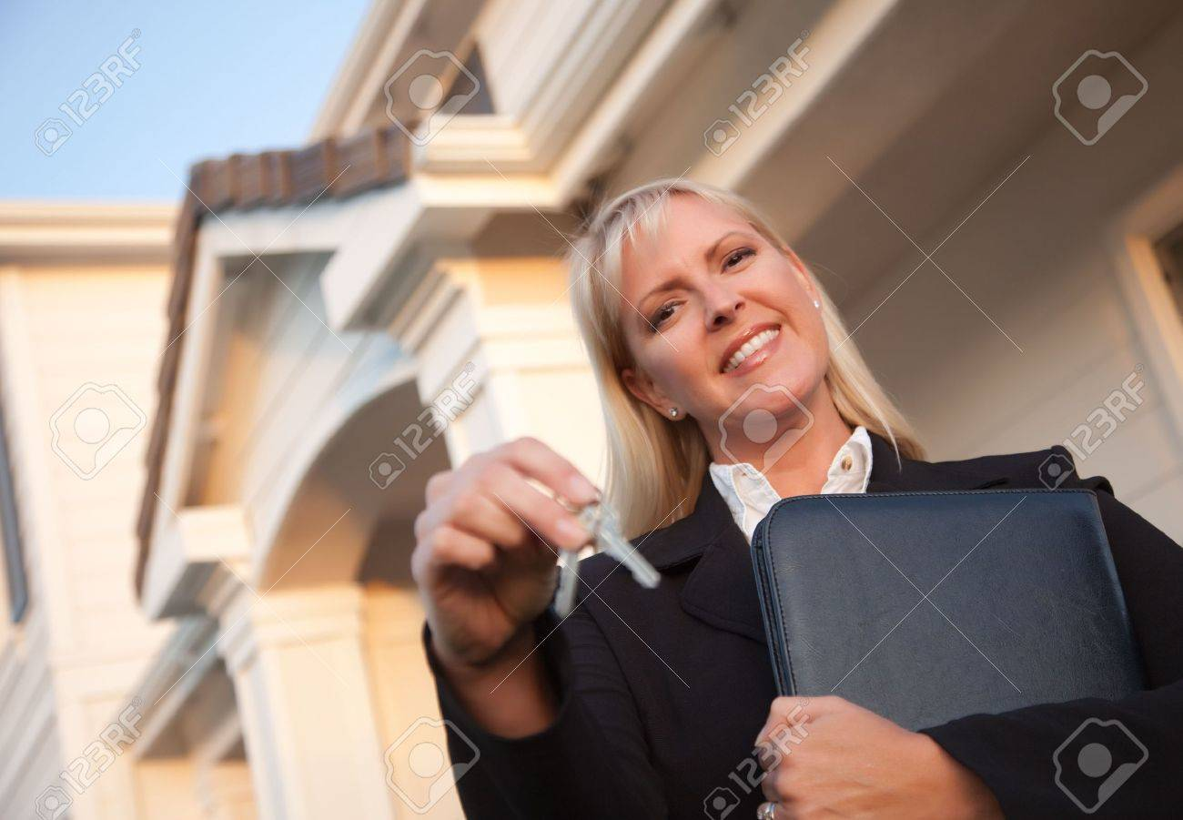 Female Real Estate Agent Handing Over Keys in Front of Beautiful House. Stock Photo - 5841607