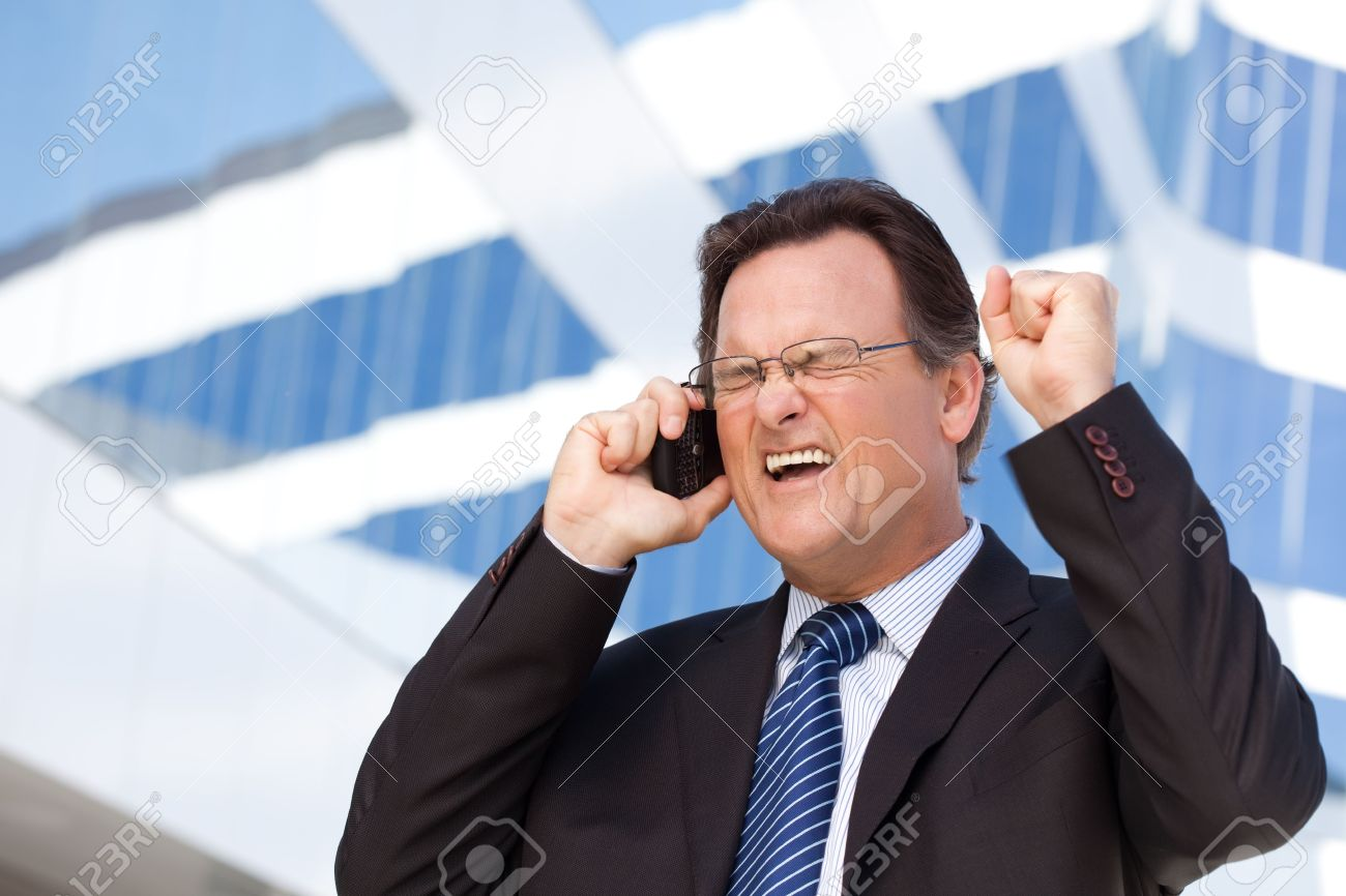 Excited Businessman Using Cell Phone Clinches His Fist in Joy Outside of Corporate Building. - 6633587