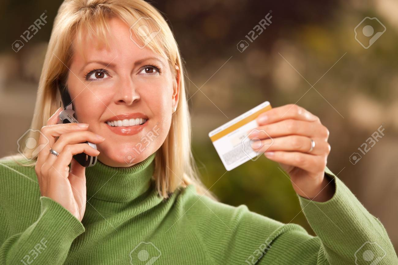 Cheerful Smiling Woman Using Her Phone with Credit Card in Hand. Stock Photo - 6810868