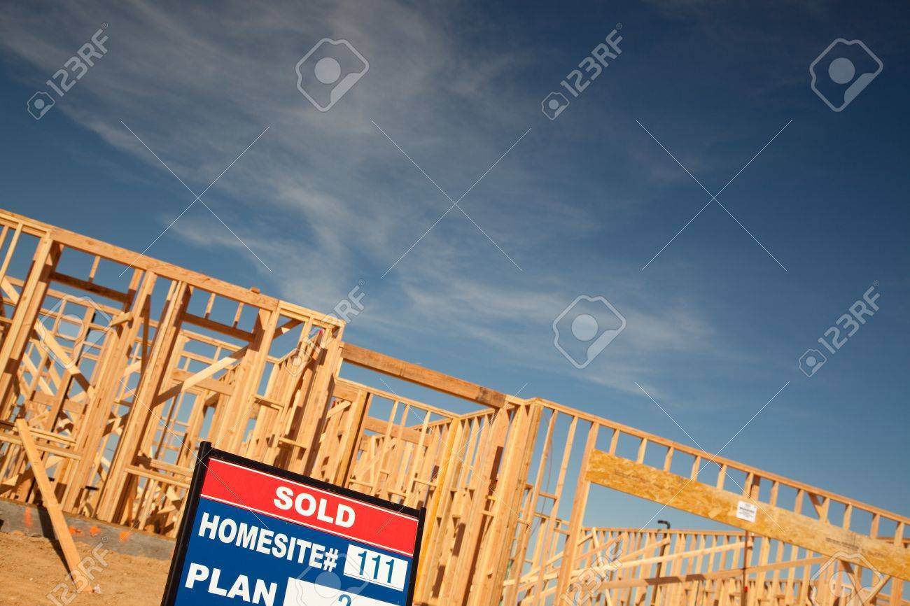 Sold Lot Real Estate Sign at New Home Framing Construction Site Against Deep Blue Sky. Stock Photo - 6971215