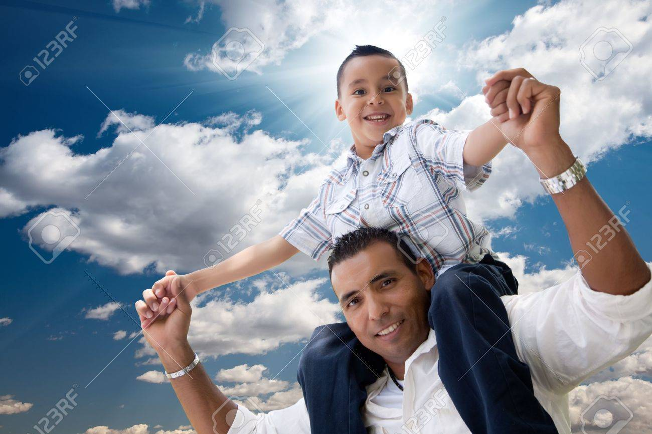 Hispanic Father and Son Having Fun Over Clouds and Blue Sky with Sun Rays. Stock Photo - 7303200