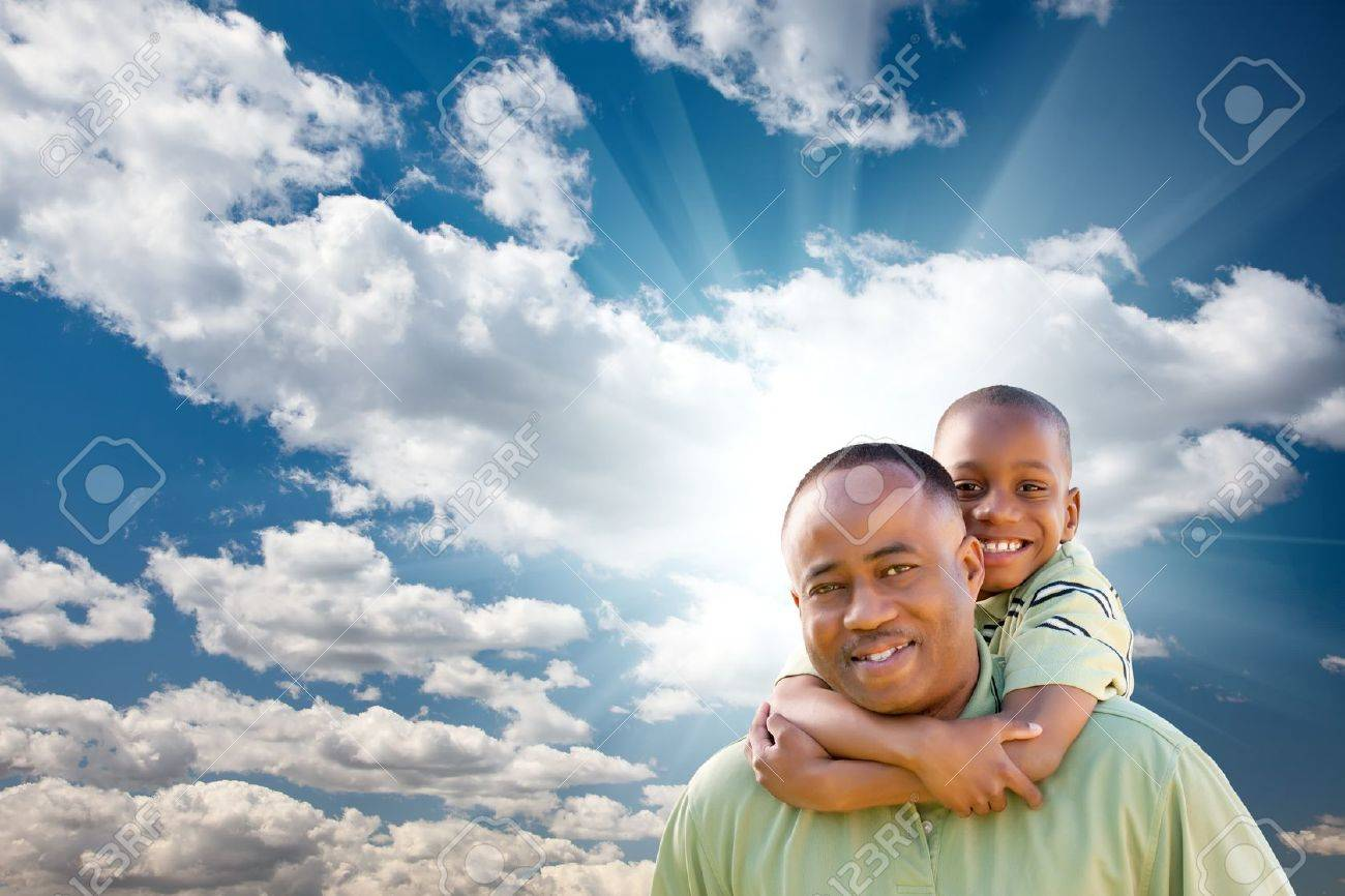 Happy African American Man with Child Over Blue Sky, Clouds and Sun Rays. Stock Photo - 7303203