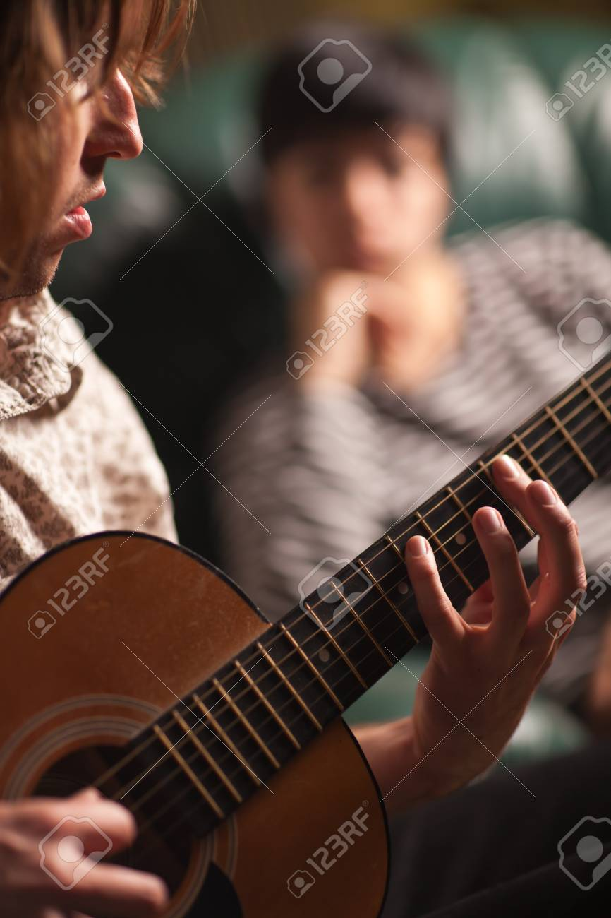 Young Musician Plays His Acoustic Guitar as Friend in the Background Listens. Stock Photo - 7968466
