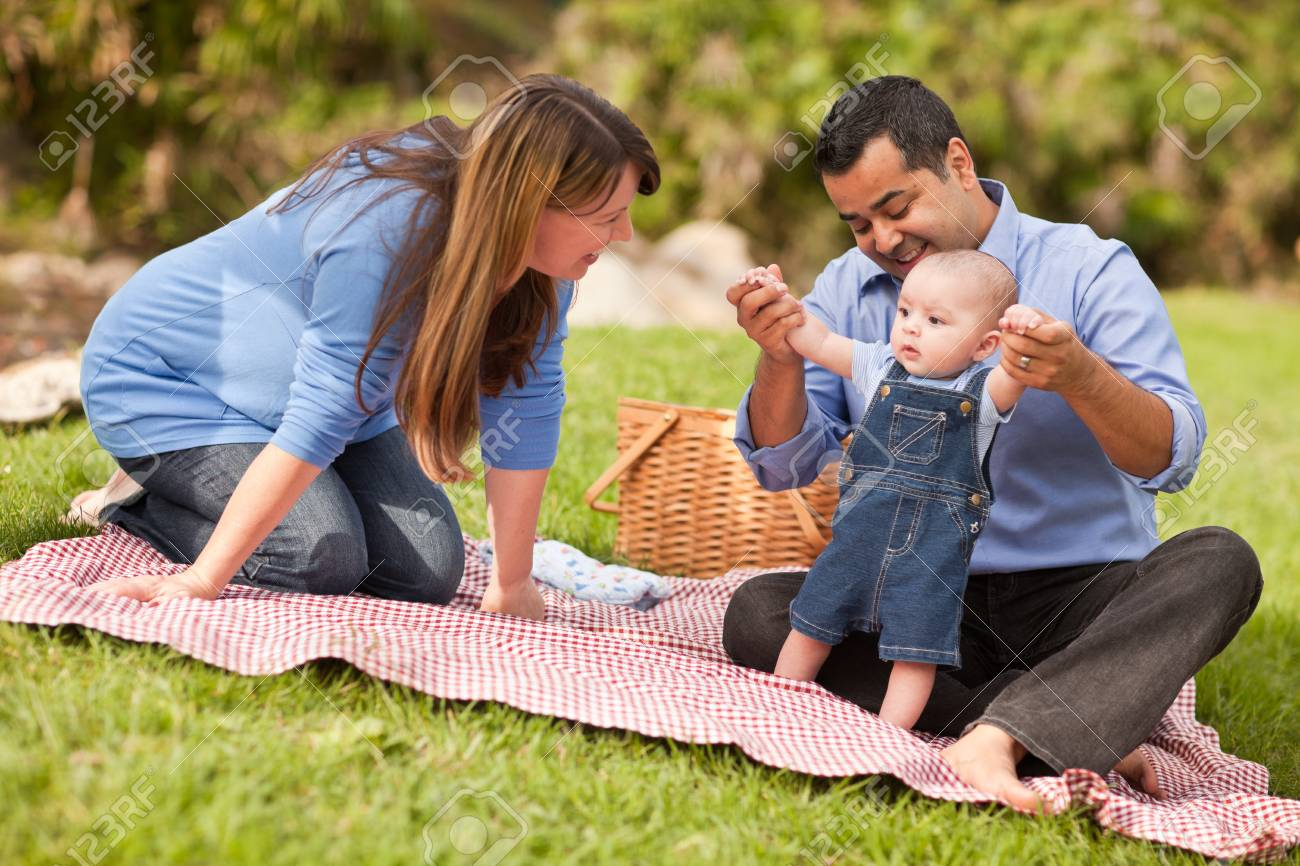 Happy Mixed Race Family Having a Picnic and Playing In The Park. Stock Photo - 8085216