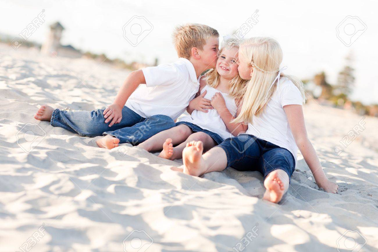 Adorable Sibling Children Kissing the Youngest Girl at the Beach. Stock Photo - 8253373
