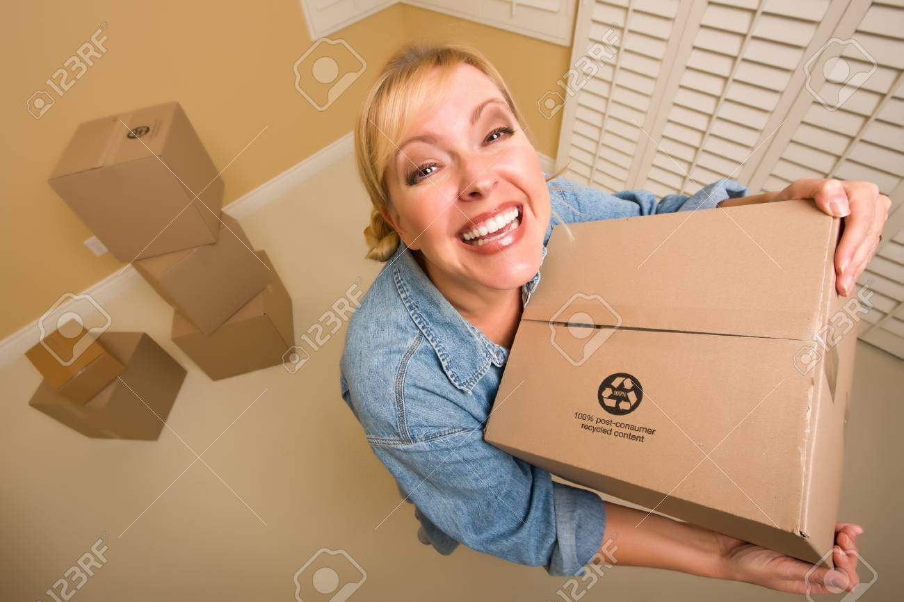 Excited Woman Holding Moving Boxes in Empty Room Taken with Extreme Wide Angle Lens. Stock Photo - 8688916