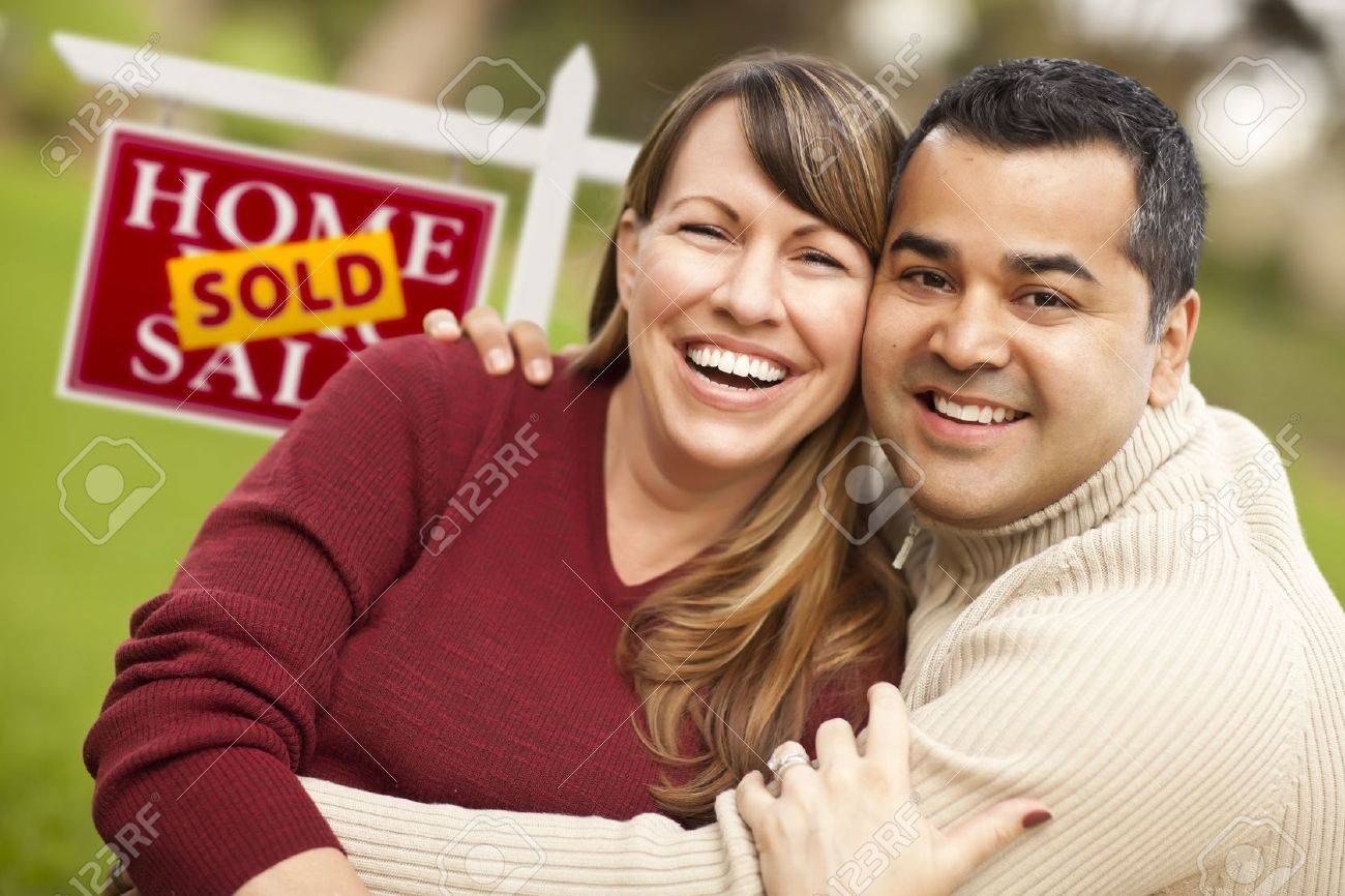 Happy Mixed Race Couple in Front of Sold Real Estate Sign. Stock Photo - 9589943