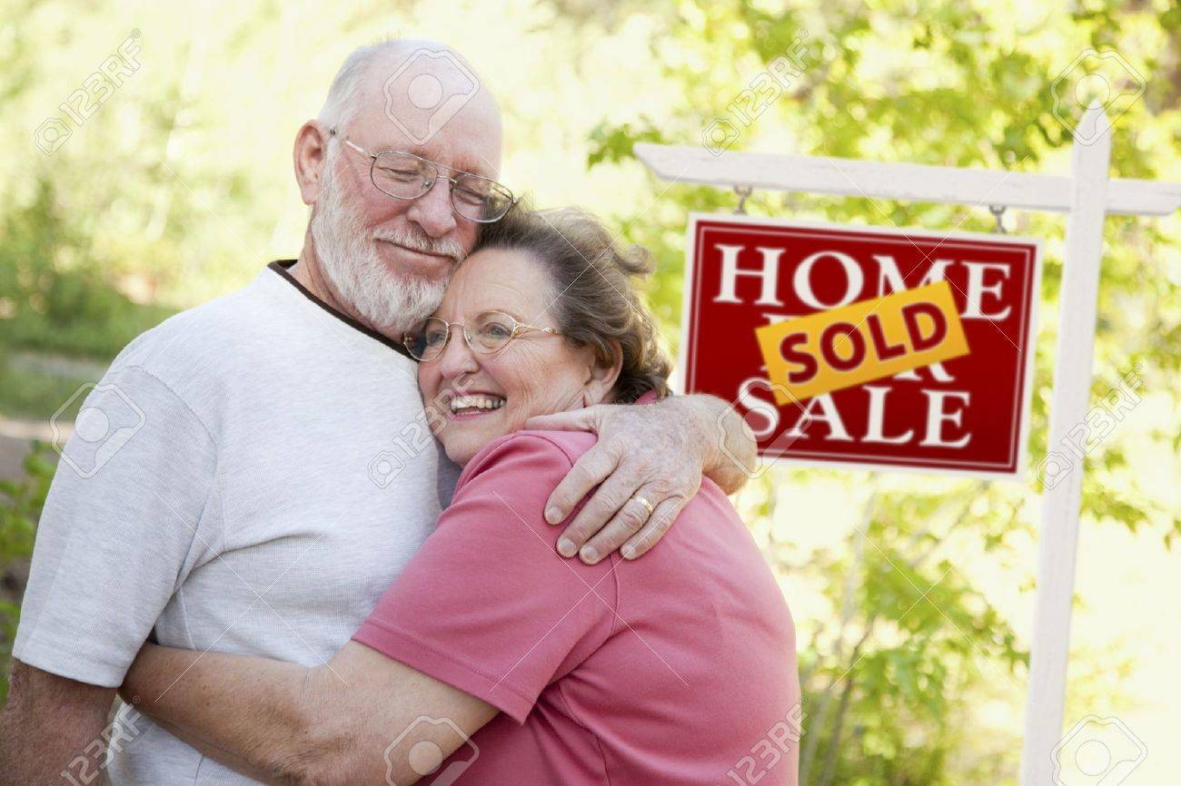 Happy Affectionate Senior Couple Hugging in Front of Sold Real Estate Sign. - 9589919