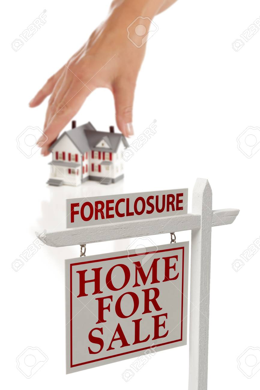 Womans Hand Choosing House with Foreclosure Home For Sale Real Estate Sign in Front Isolated on White. Stock Photo - 9643221