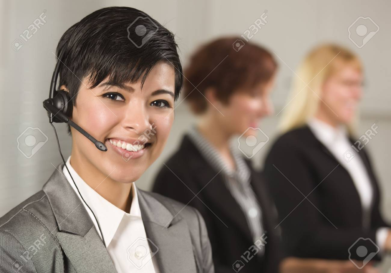 Pretty Hispanic Businesswoman with Colleagues Behind in an Office Setting. Stock Photo - 10244689