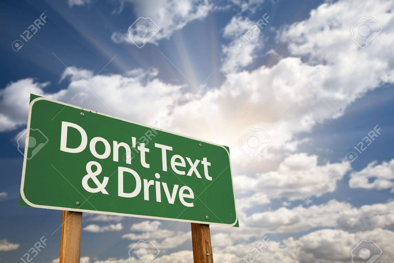 Don't text and Drive Green Road Sign with Dramatic Sky, Clouds and Sun. - 10577222