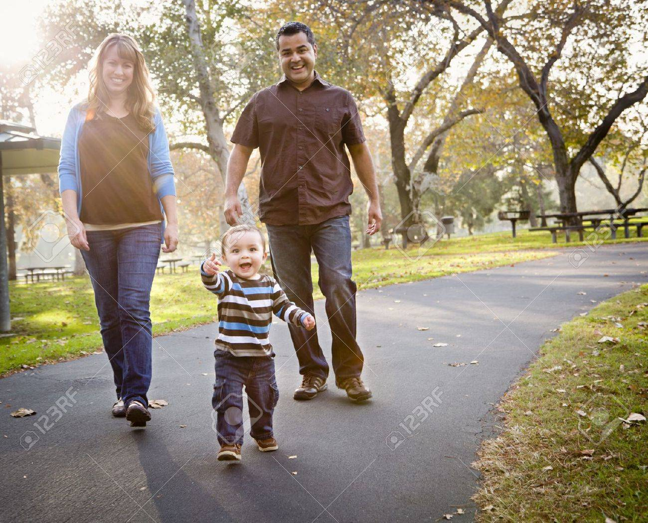 Happy Young Mixed Race Ethnic Family Walking In The Park. Stock Photo - 11396012