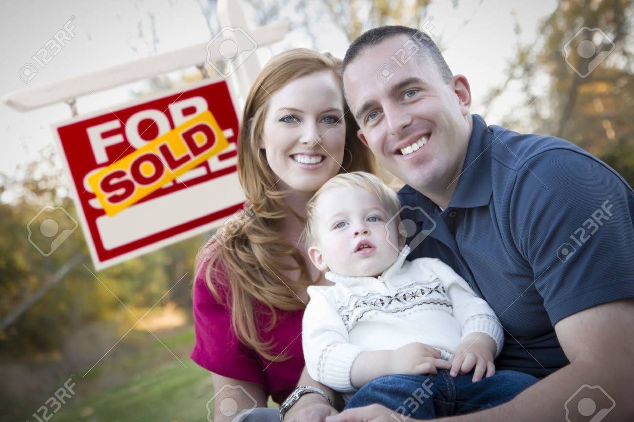 Happy Young Caucasian Family in Front of Sold Real Estate Sign. Stock Photo - 12837958