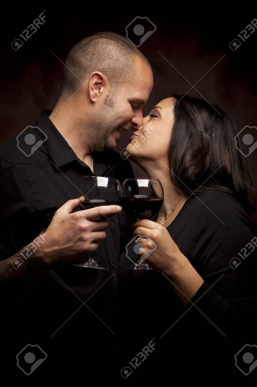 Happy Young Mixed Race Couple Holding Wine Glasses Against A Black Background. Stock Photo - 13237485