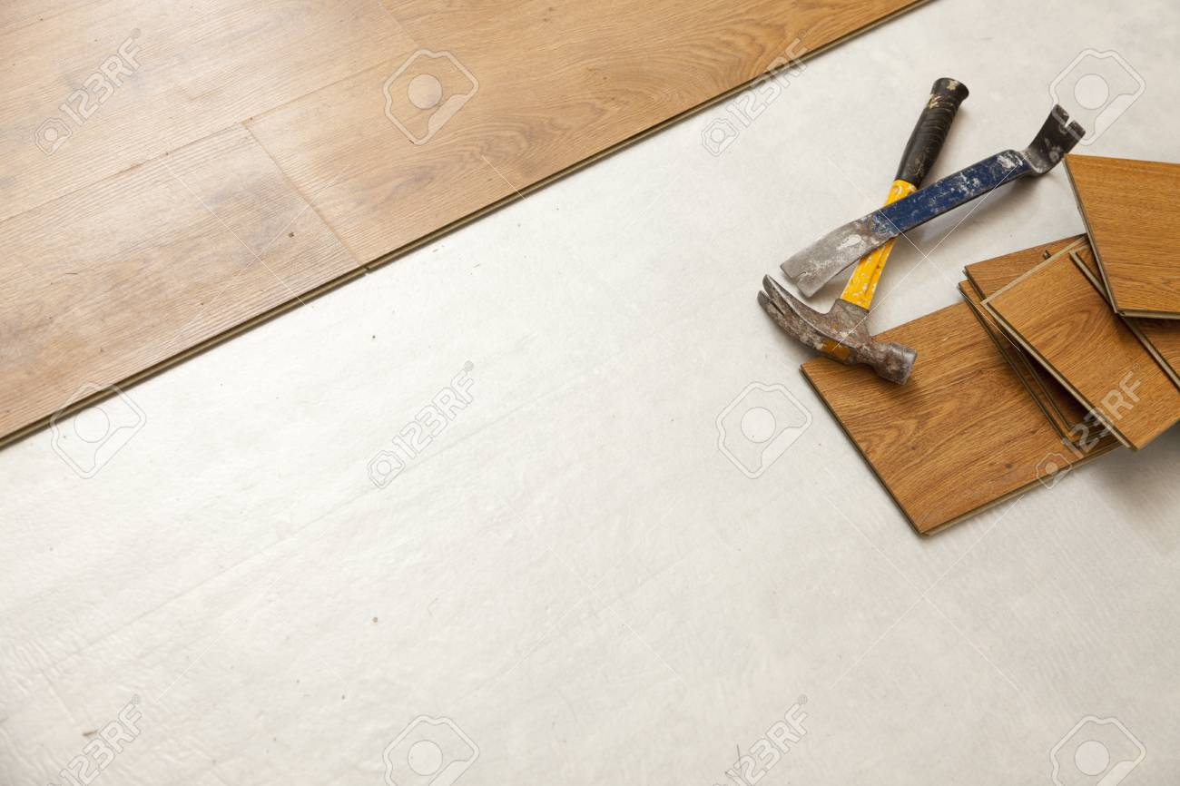 worn hammer and pry bar with laminate flooring abstract with.. stock