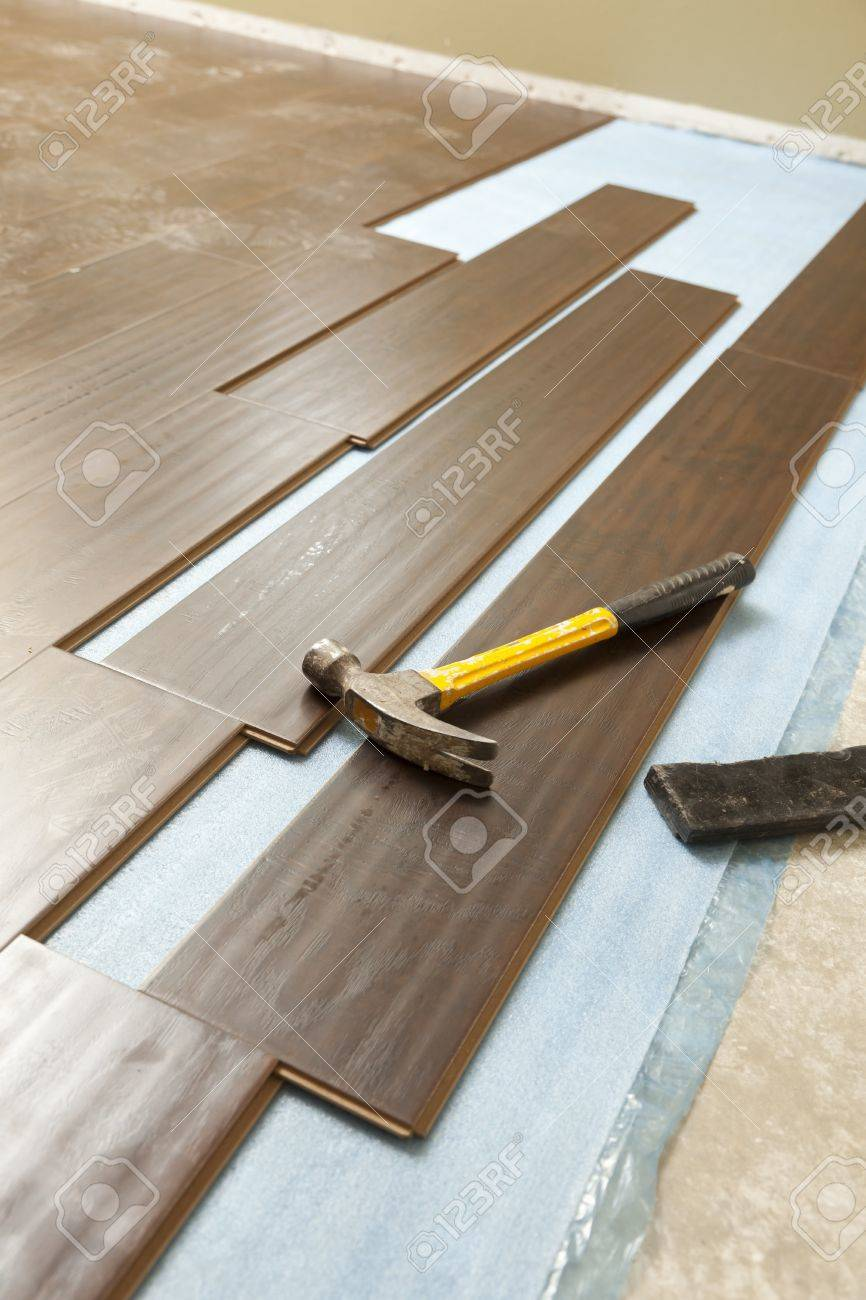 hammer and block with new laminate flooring abstract. stock photo